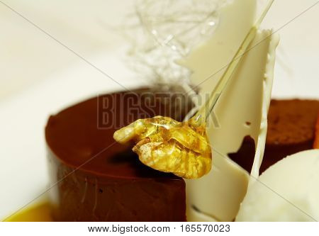 Dark chocolate cake or mousse with caramelized walnut sugar candy on plate on white blurred background. Modern molecular gastronomy