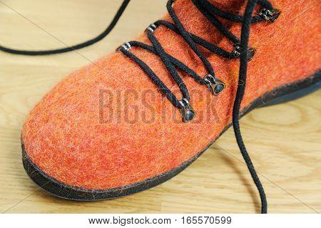 Orange Felt shoes with black lace. Close up.