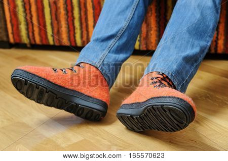 Orange felt shoes on the feet of a man.