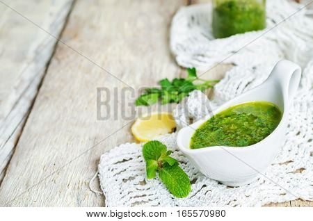 Mint parsley green sauce on wood background.