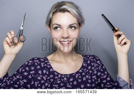 Young female hairdresser with scissors and comb advertising for a cosmetology school or a salon. The image depicts trendy styles and hair color.