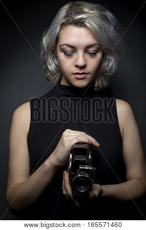 Female actor posing with a vintage camera as an artistic director creative cinematographer or filmmaker. She is advertising the Hollywood movie industry or film art schools.
