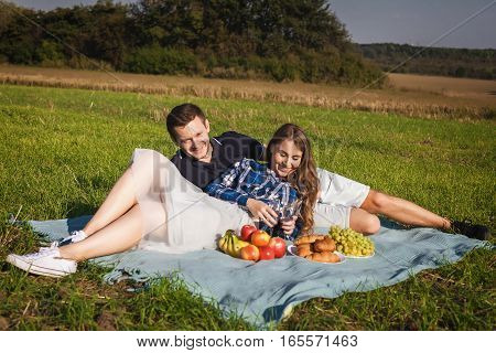 young happy couple at picnic on the green grass with bananas, apples, wine and grapes