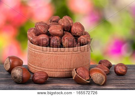 hazelnuts in a wooden bowl on a dark board with blurred garden background.