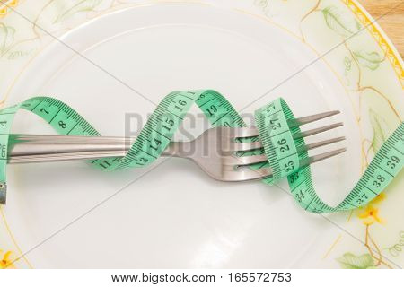 Empty plate with measure tape knife and fork. Diet food on wooden table