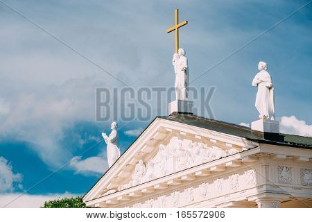 Vilnius Lithuania. Close Pediment Of Cathedral Basilica Of St. Stanislaus, St. Vladislav With Three Statues: St. Elena With Cross, St. Stanislaus, St. Casimir, Relief Sculpture Decoration, Blue Sky
