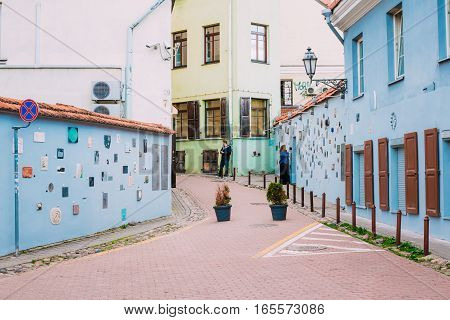Vilnius, Lithuania - July 7, 2016: People walks on Literatu Street - one of the oldest streets in the Old Town of Vilnius, Lithuania. Wall c literary works of art. Literatu Street Wall.