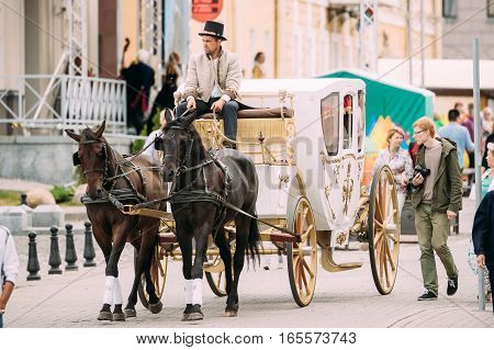 Minsk, Belarus - September 3, 2016: Holiday carriage drawn by two horses, controlled by a coachman dressed in clothes of 19th century ago, celebration of Day of Minsk city in a historic area Nemiga