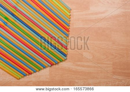 Colorful drinking straws on a beige background.