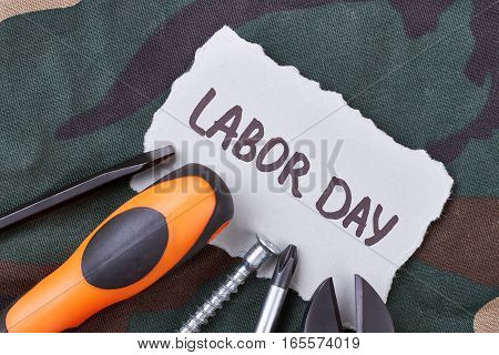 Labor Day card and tools. Screwdrivers on camouflage fabric. Greet the laborers.