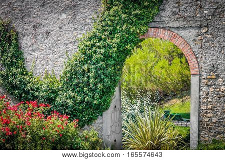 Park entrance with roses and ivy vine on wall.
