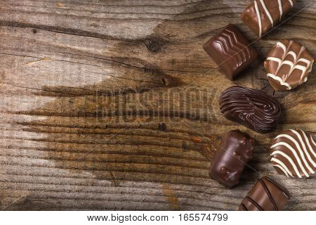 Different types of chocolate candy over rustic wooden background with copy space