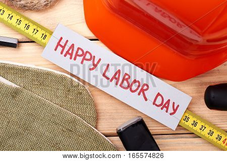 Tools around Labor Day card. Tape measure, hard helmet, rope. Organisation of celebration.