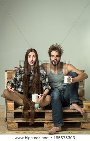 Young surprised couple of pretty girl or cute woman with brunette long hair and handsome man or muscular macho with muscular torso sits on wooden with tea cups pallet sofa on grey background
