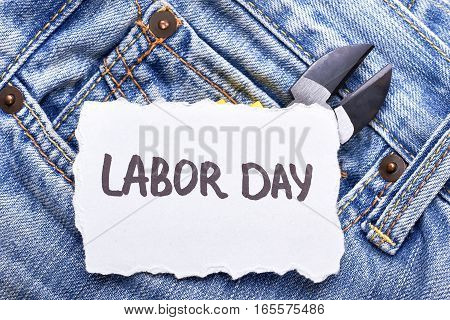 White Labor Day greeting paper. Card with pliers on jeans. Joy and festive mood.