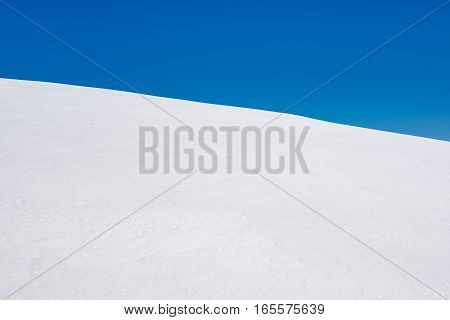 Winter natural background of pure snow with blue sky.
