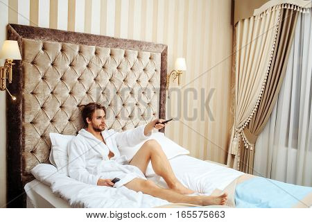 young handsome bearded man in white terry bathrobe laying on bed in hotel bedroom and watching tv with remote control