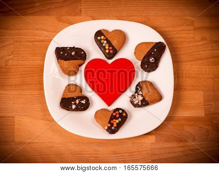 Heart cookies on a wooden brown background. Concept of Holiday Valentine's Day or Christmas and New Year. Top view of assorted cookies covered with chocolate, gift for Valentines Day.