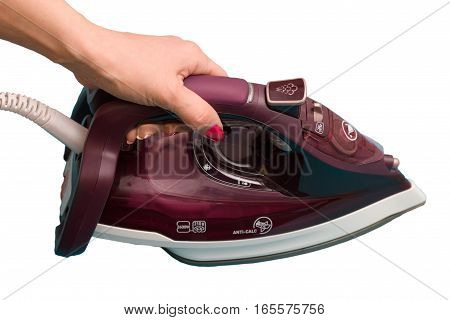 Steam iron in a female hand isolated on white background.