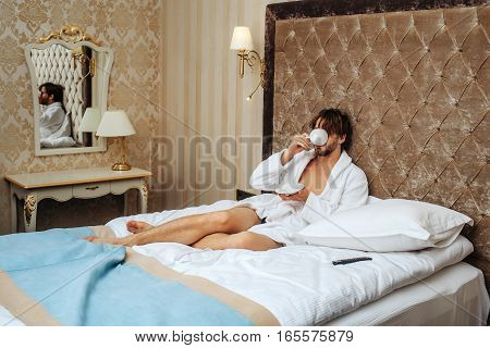 Bearded Man On Bed With Coffee