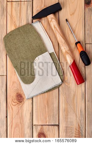 Hammer and screwdriver on wood. Work gloves near tools. How to become a handyman.