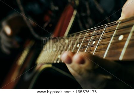 Guitar fret to the point. The hands on the strings of a guitar fretboard. Guitarist play chords on a musical instrument.