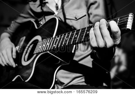 Guitarist with guitar. The hands on the strings of a guitar fretboard. Accord on a musical instrument. Shallow depth of field.