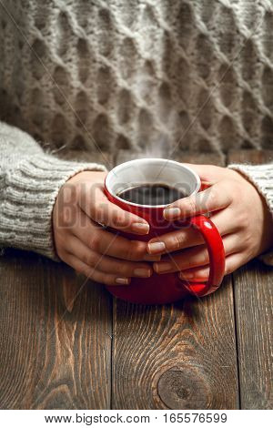 The girl in a cozy knitted sweater drinking coffee from a red mug, sitting at a vintage wooden table