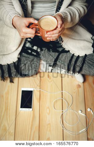 Girl with a cup of coffee sitting on a wooden floor. top view