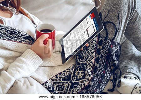 Woman in home cozy clothes sitting on a sofa using tablet with headphones, holding a red cup of coffee hands. Online education concept. e-learning.