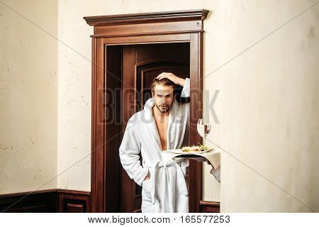 young handsome bearded man in white terry bathrobe stands at wooden door in hotel near human hand of waiter with food and water glass on tray
