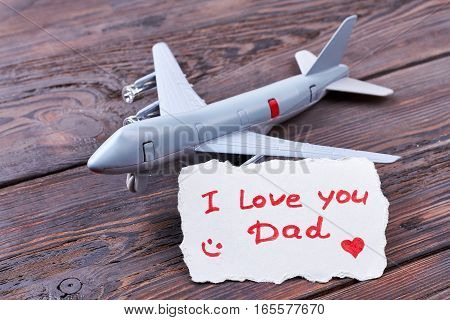 Toy plane and Dad's card. Toy jet on wooden background. Share your love with father.