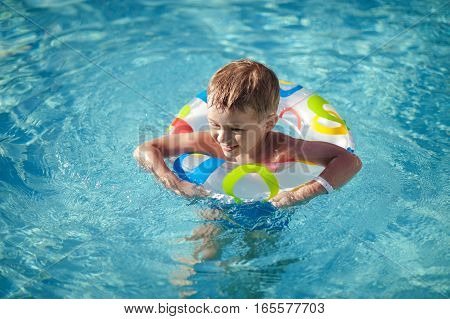 Happy Little caucasian boy learning swim with saver in pool, teeth smiley boy with a life ring enjoying life in the swimming pool.