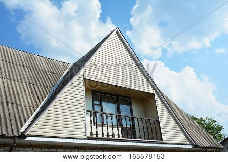 Gable and Valley type of roof construction with cozy balcony. Building attic house construction with different types of roof designs