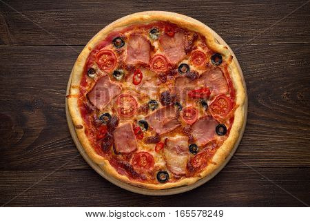 Homemade Italian Pizza With Ham, Tomatoes, Olives, Cheese On Dark Rustic Wooden Background.