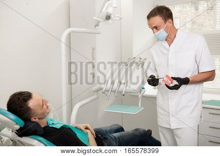 European dentist talking to patient, sitting in the chair in dental clinic. stomatology and health care concept