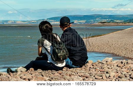 Happy young couple in love relaxing in a beach of Minehead UK enjoying ocean view together sitting in the sand embracing and hugging.