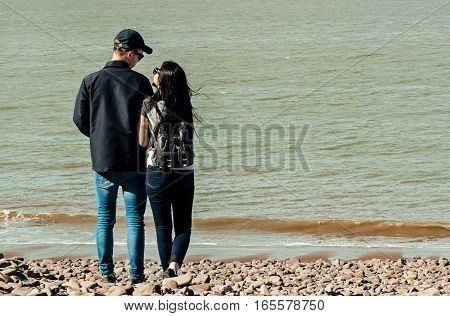 A happily couple in a beach shore holding hands and looking each other in Minehead UK.