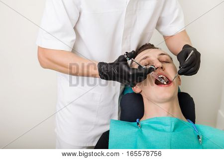 dentist makes anesthetizing injection within a patient's mouth, using dental instruments.