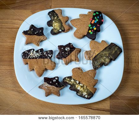Cookies on a white plate, wooden brown background. Christmas tree or stars shaped cookies. Top view of assorted cookies covered with chocolate and decorated with, gift for winter Holidays.