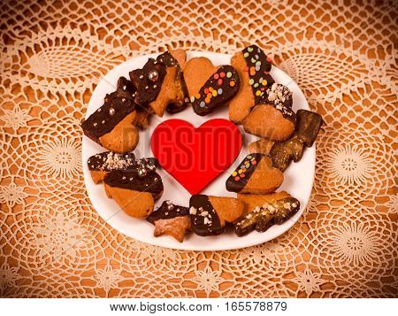 Heart cookies on a lace table cloth background. Concept of Holiday Valentine's Day or Christmas and New Year. Top view of assorted cookies covered with chocolate, gift for Valentines Day.