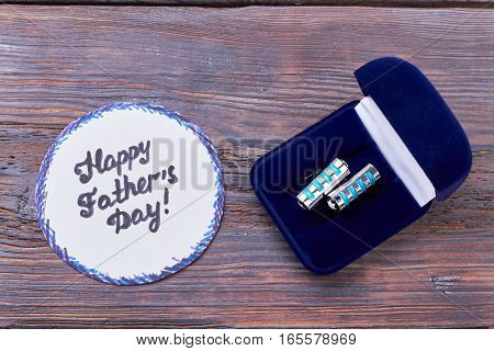 Father's Day card and cufflinks. Greeting card near cufflink box. Expensive present for dear dad.