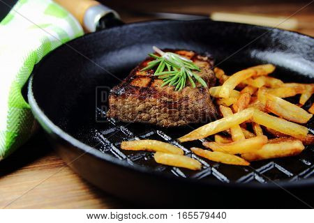 beef steak with rosemary and French fries in the pan