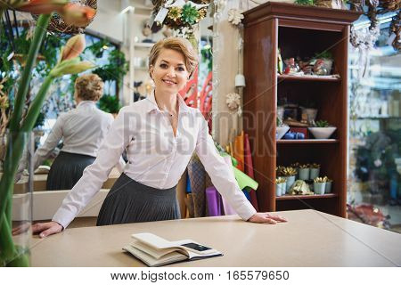 Welcome to my store. Happy female florist is standing at counter and smiling. She is looking at camera with hospitality