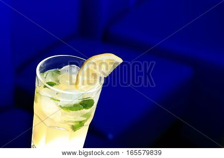 Glass Of Lemonade With The Slice Of Lemon And Mint. Dark Blue Blurred Background