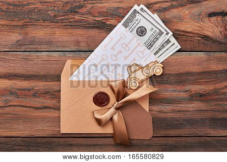 Money in envelope with seal. Key print paper near bow. Money is base of economy.