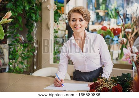 Happy female florist is listening to client attentively. She is making notes and smiling
