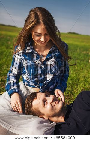 man and woman sitting on the grass and smiling. his head in her lap