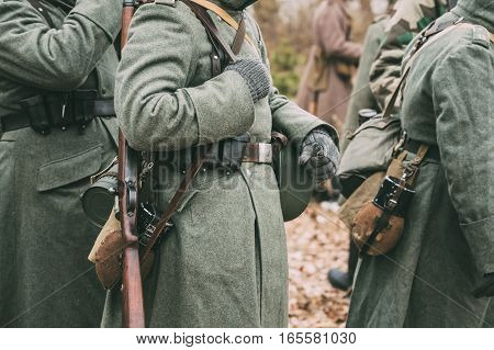 Close up of German military ammunition of a German soldier at World War II. Warm autumn clothes, soldier's overcoat, gloves, helmet, pouch, sapper shovel, flask, rifle, storage box case for gasmask.