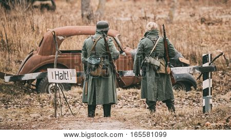 Two Unidentified Re-enactors Dressed As German Infantry Wehrmacht soldier at World War II are on patrol in autumn field.